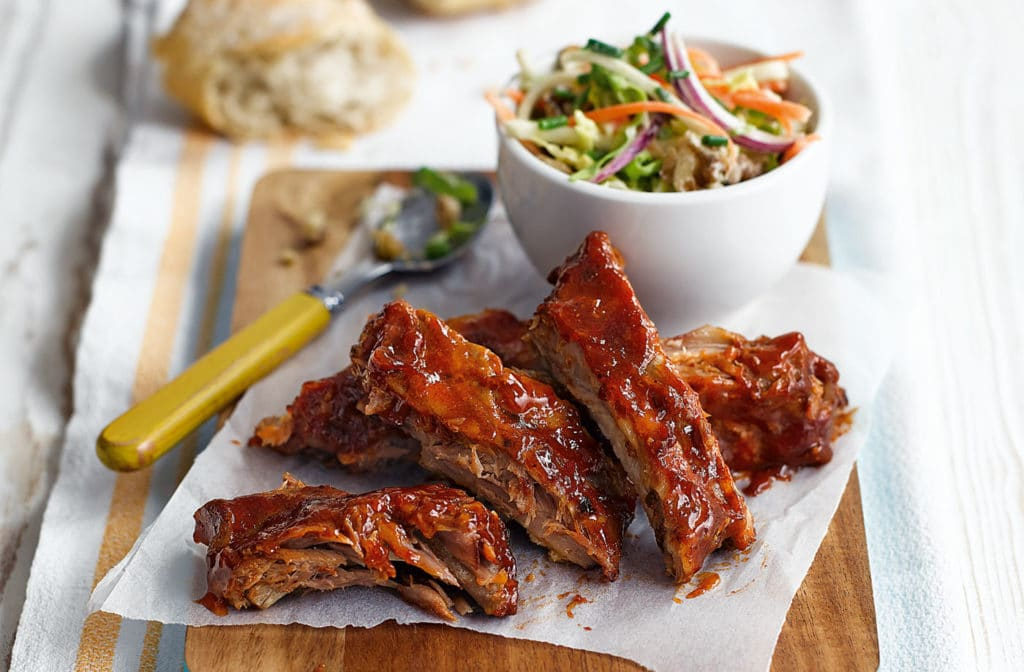 A plate of cut teriyaki ribs with a bowl of coleslaw
