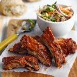 A plate of cut ribs with a bowl of coleslaw