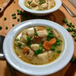 two bowls of chicken stew with potato dumplings