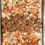 a sheet pan of sausage and sliced vegetables