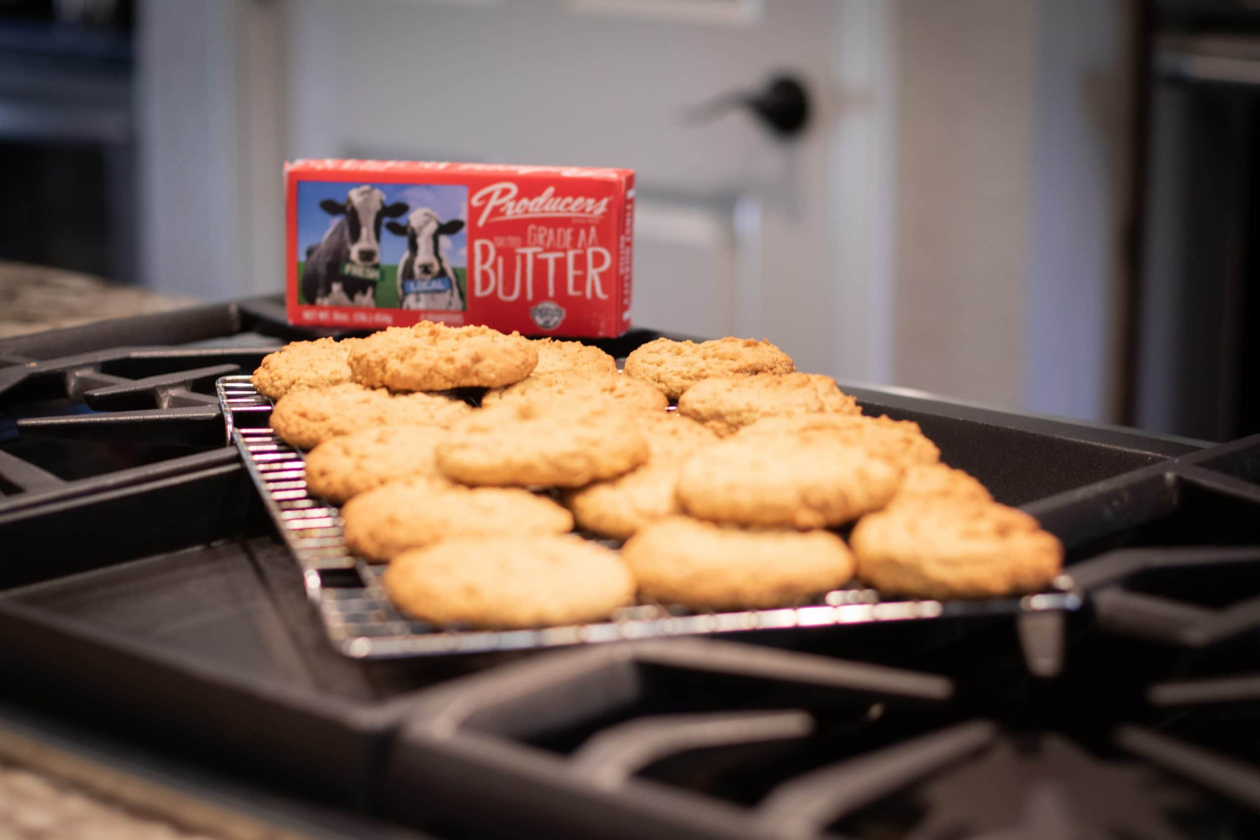 a cooling rack of cookies from the oatmeal cookie recipe with a red box of butter from Producers Dairy