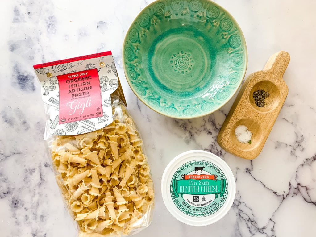 Ingredients for lasagna soup recipe are shown Trader Joe's Gigli pasta and ricotta cheese with a green bowl from Anthropologie