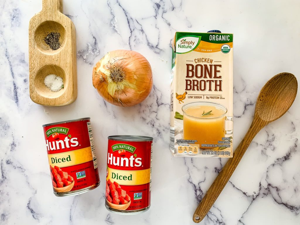 Instant Pot lasagna soup recipe are shown Hunts diced tomatoes an onion and Simply Nature chicken bone broth and a wooden spoon
