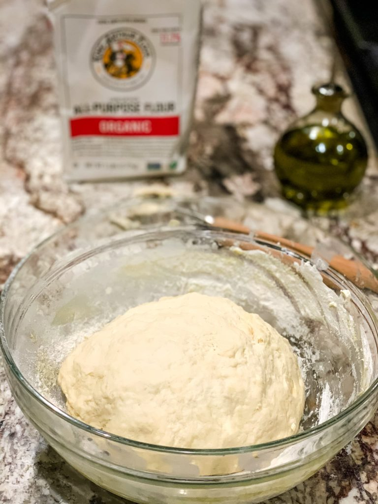 a bowl of rising dough with a bag of King Arthur flour and a bottle of olive oil in the background