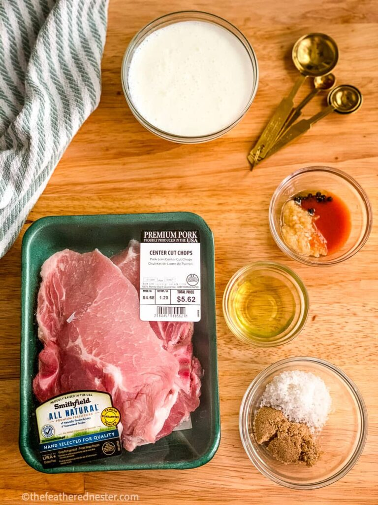 A package of pork chops and the ingredients to make buttermilk brined pork chops. A bowl of buttermilk, olive oil, and spices.