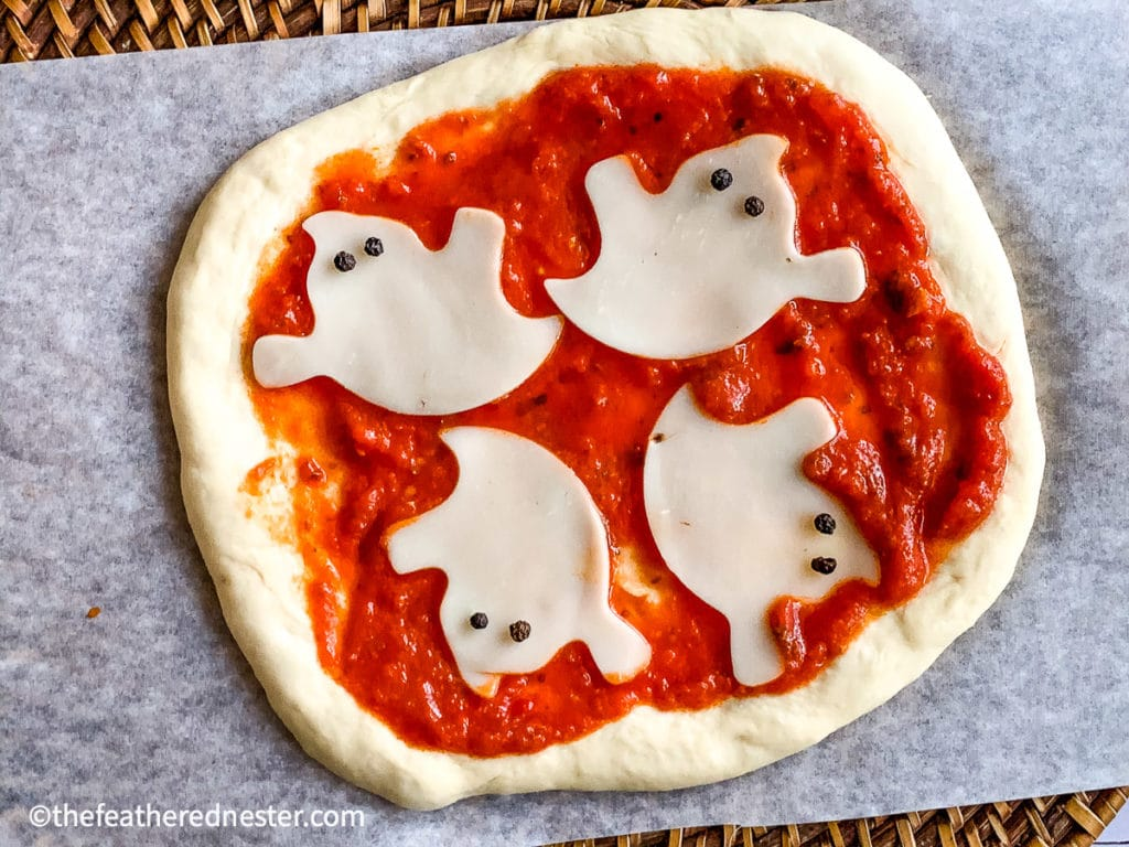 Cheese mini pizza with cheese shaped ghosts for halloween