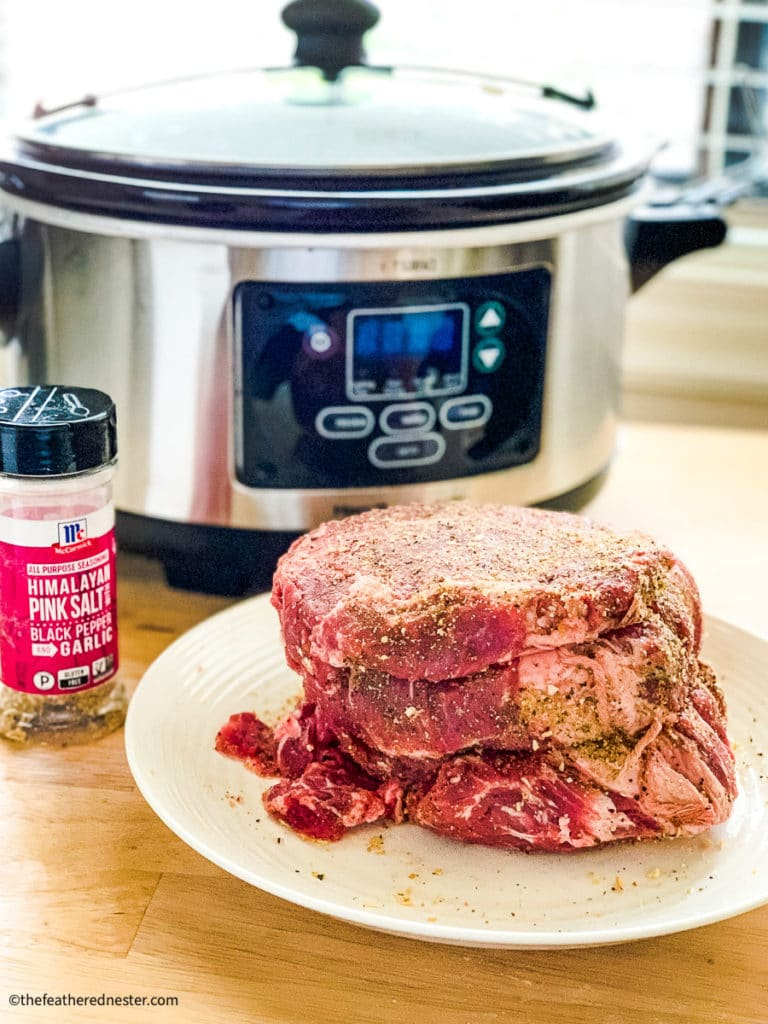 seasoned beef roast with a crock pot and McCormick all purpose seasoning in the background