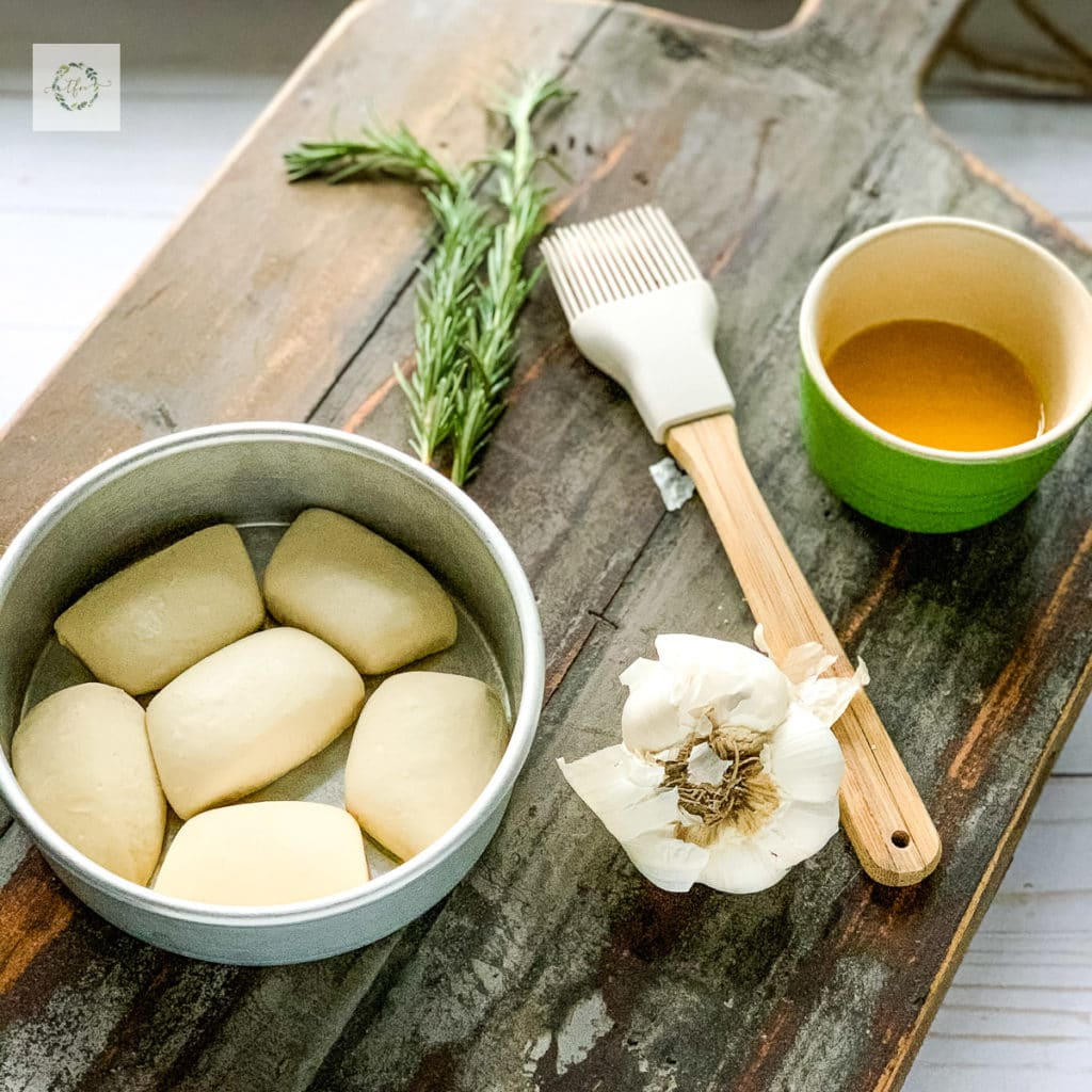 a wooden board with a frozen bread dough rolls in a round baking dish with a pastry brush and green bowl of melted butter and head of garlic