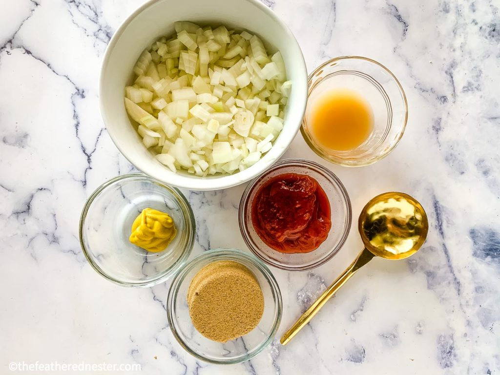 some of the ingredients to make the sauce for this dried beans recipe, a bowl of chopped onions, mustard, ketchup, brown sugar and a gold spoon to mix them