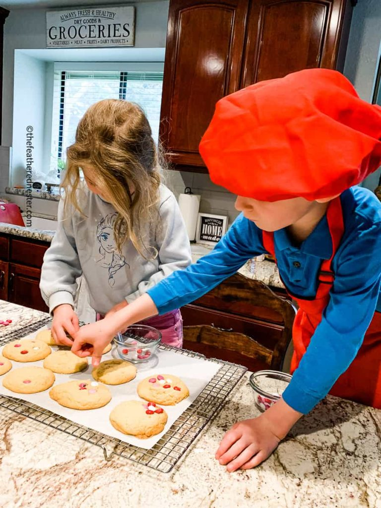 two children pressing m&m candies into cookies