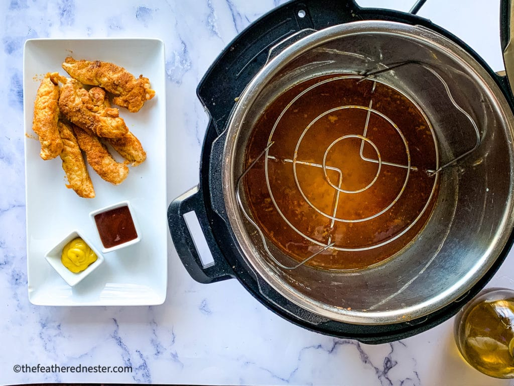 cooked tenders on a platter with dipping sauces next to the pressure cooker