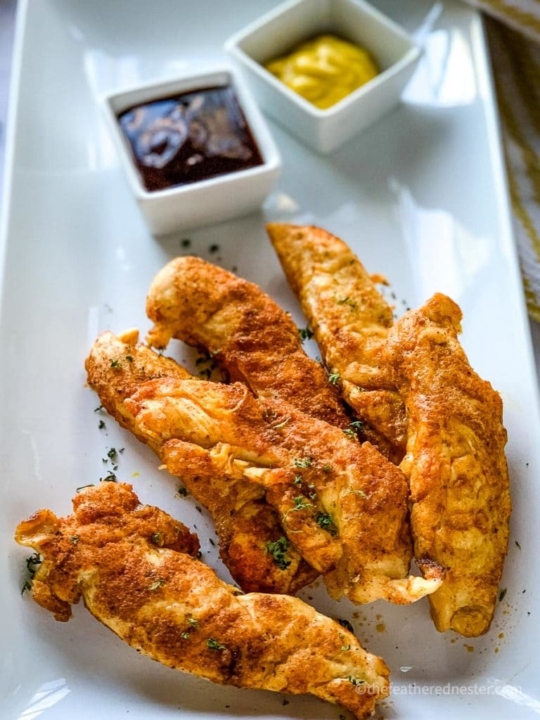 a plate of Instant Pot Chicken Tenders with honey mustard and barbecue dipping sauces