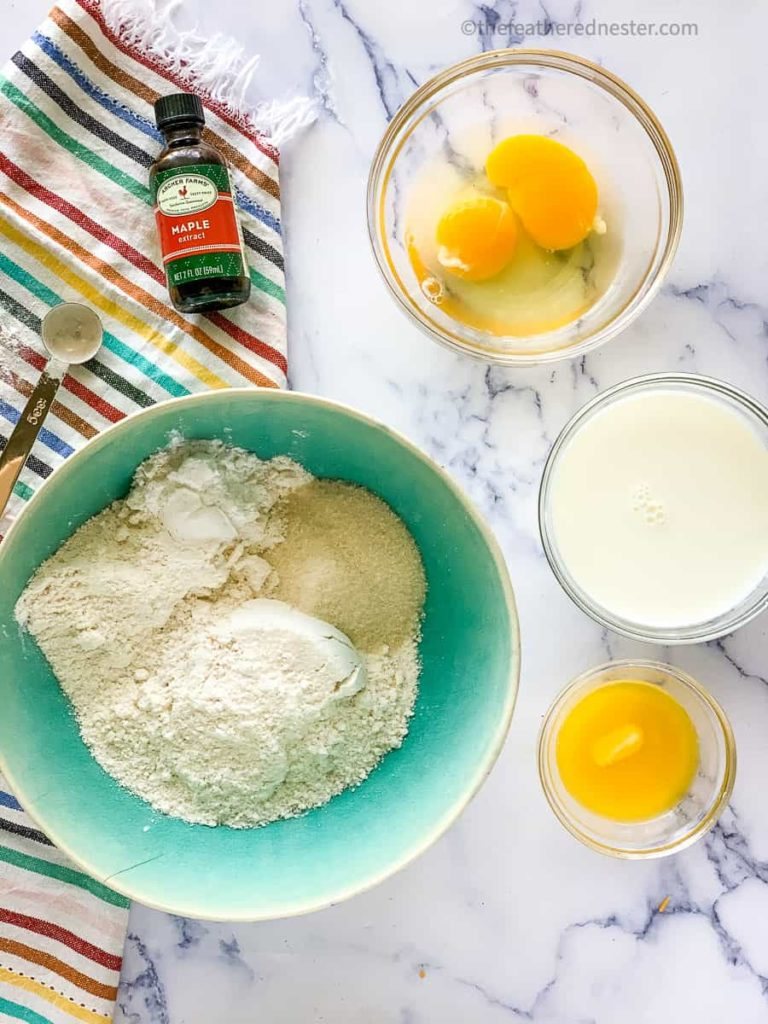 dry ingredients in a green bowl with eggs milk and melted butter in smaller bowls