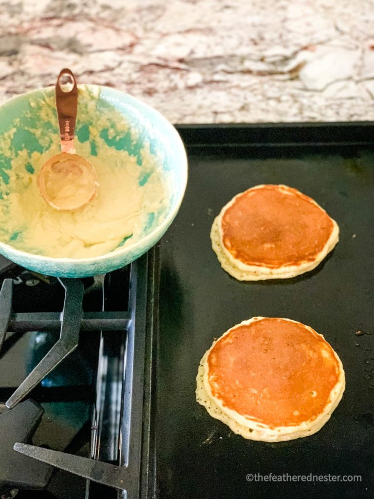 Bisquick pancakes cooking on a griddle with a bowl of batter in the background