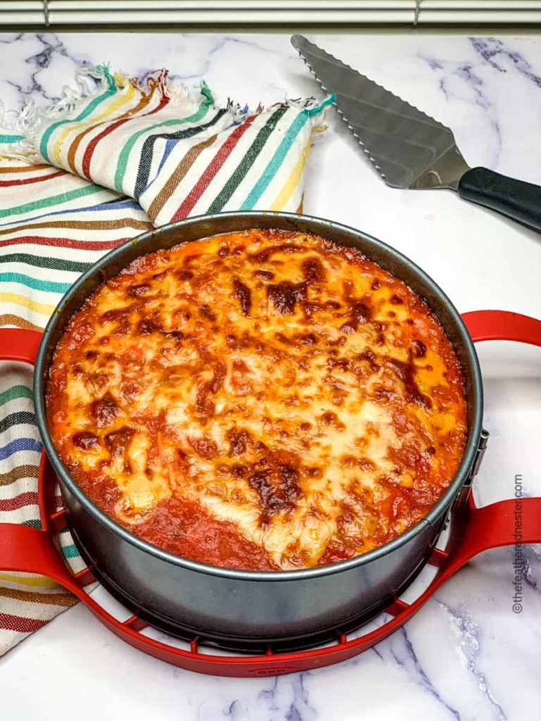 the pan Instant Pot lasagna cooling with a serving spoon and striped napkin in the background