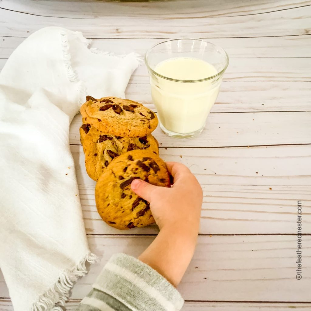 child's hand reaching for a cookie with a white cloth napkin and glass of milk in the background