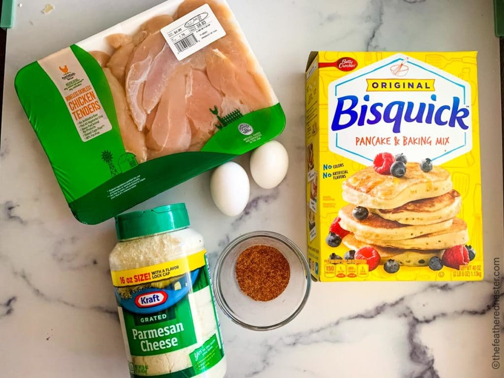 tray of chicken tender tenderloins, box of original Bisquick, two eggs, a container of grated Parmesan cheeses, and clear bowl of spices