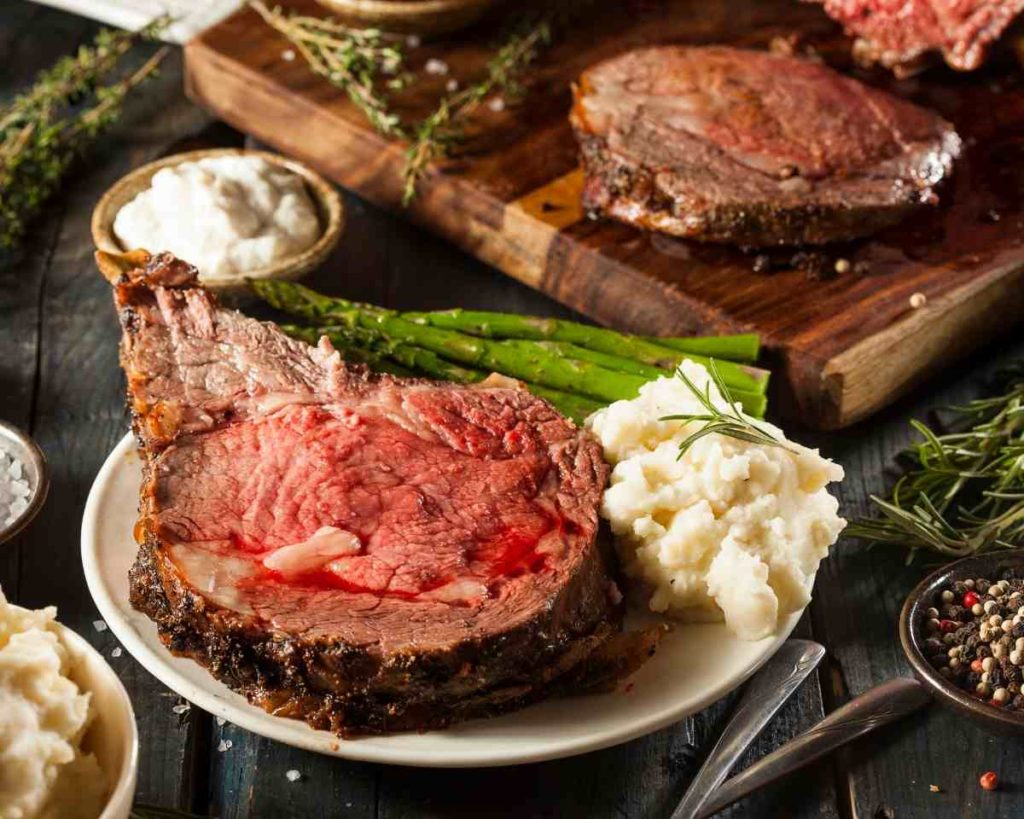 a plate of beef rib roast with mashed potatoes and asparagus with a cutting board showing a cut prime rib roast