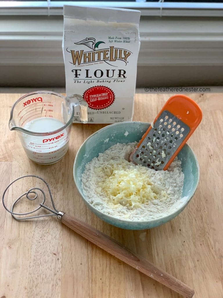 blue bowl of grated frozen butter and self rising flour with buttermilk, a bag of self rising flour and a dough whisk shown on the sides of the bowl