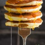 a fork holding up a stack of mini pancakes