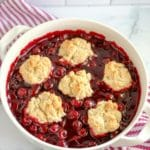a white casserole dish with easy bisquick cherry cobbler with cherry pie filling