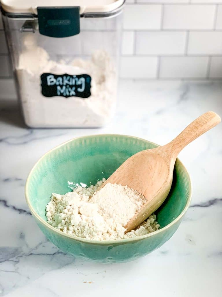 a bowl of DIY baking mix with a wooden scoop and a canister of homemade Bisquick mix in the background