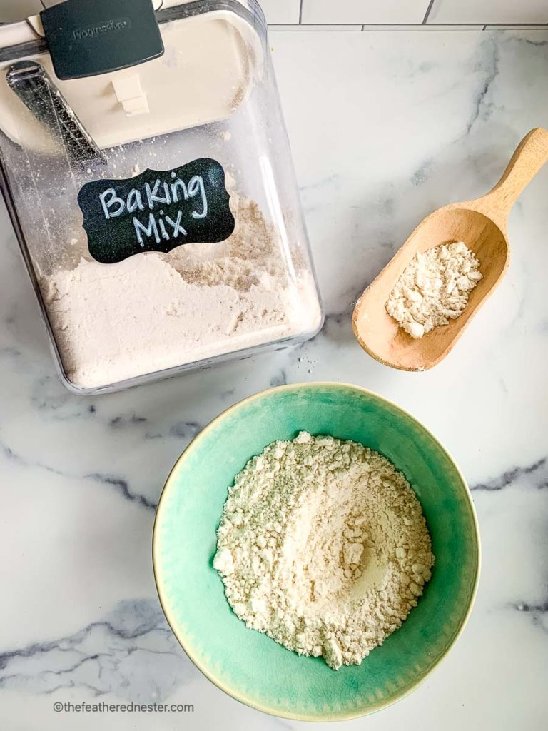 a green bowl of DIY baking mix with a Prepworks container of mixed homemade Bisquick baking mix and a wooden scoop of the scratch mix