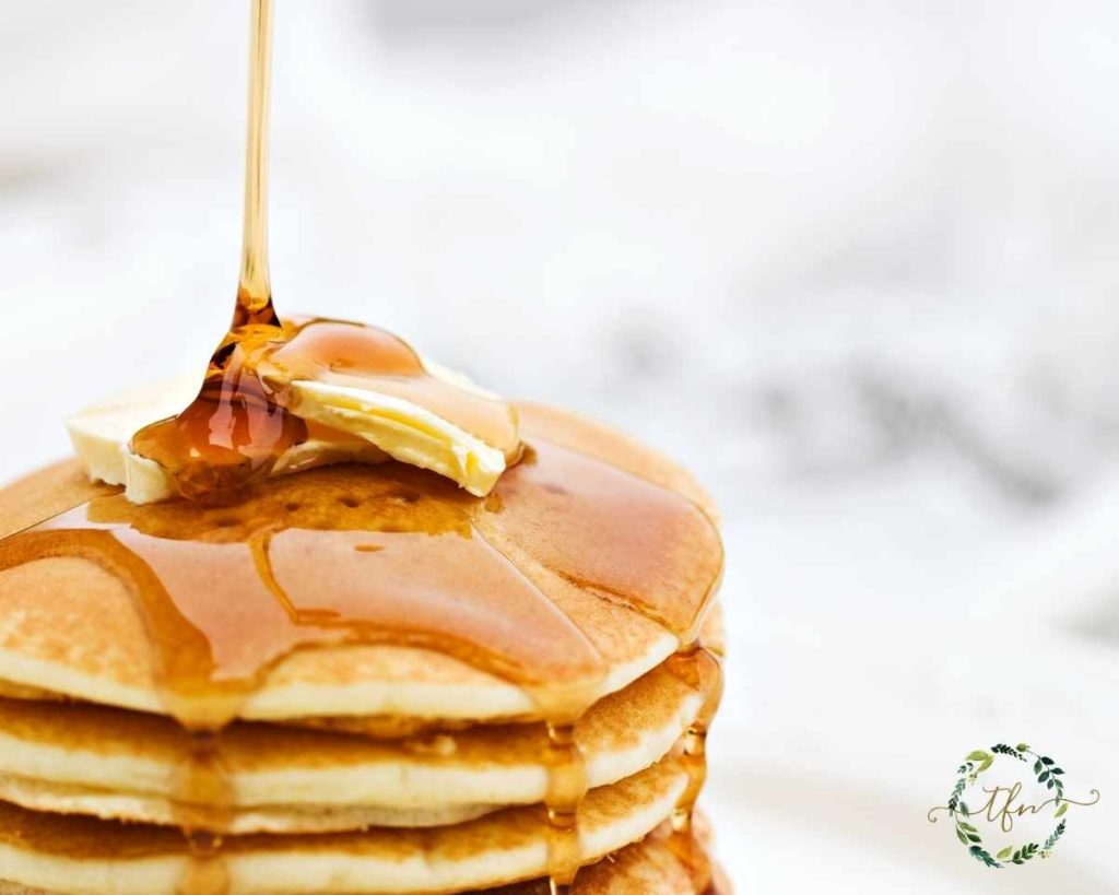 pouring syrup on a stack of Bisquick pancakes
