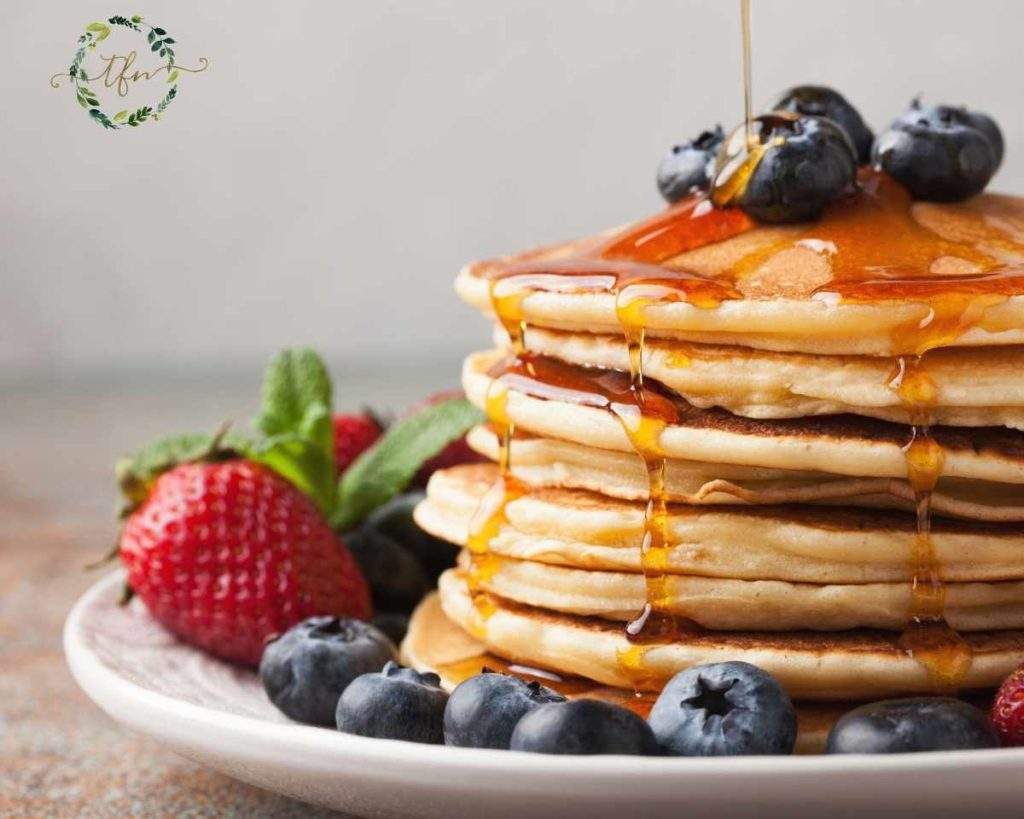 strawberries and blueberries with a stack of ultimate pancakes with syrup being drizzled over