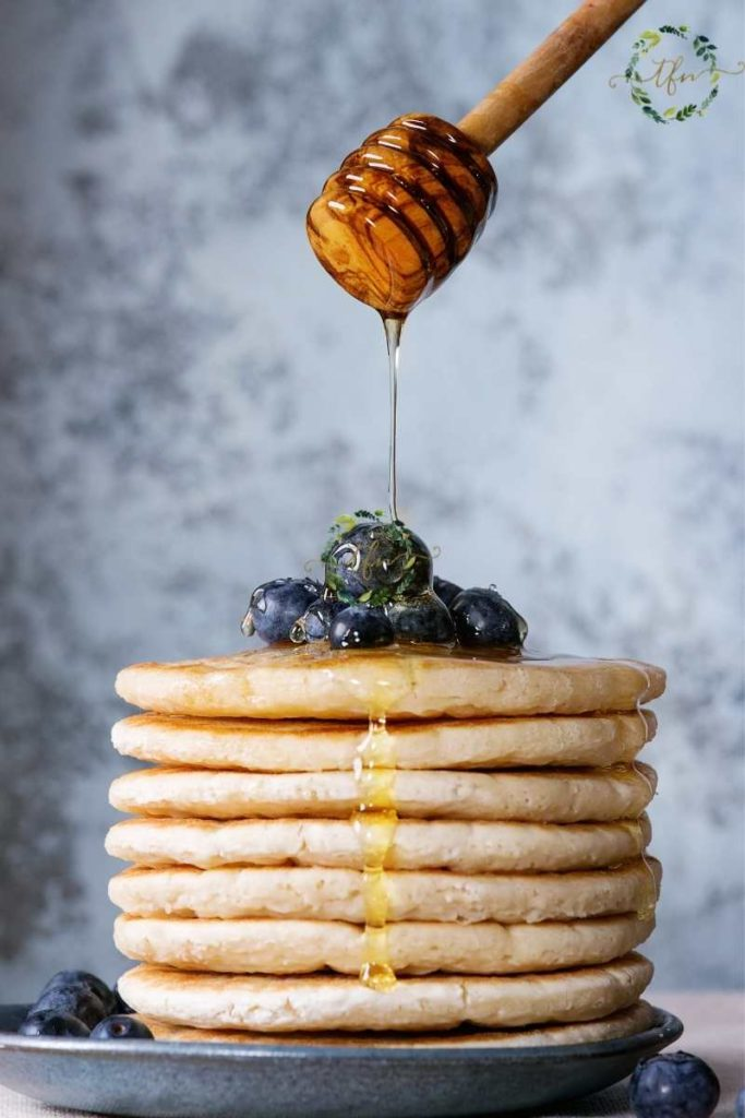 drizzling honey over a stack of pancakes and blueberries