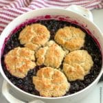 a round casserole dish of blueberry cobbler with a red and white napkin
