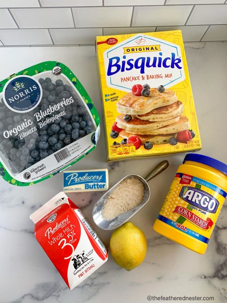 original bisquick baking mix, corn starch, a lemon, a cup of sugar, a carton of Producers milk, a stick of butter, and a carton of fresh blueberries