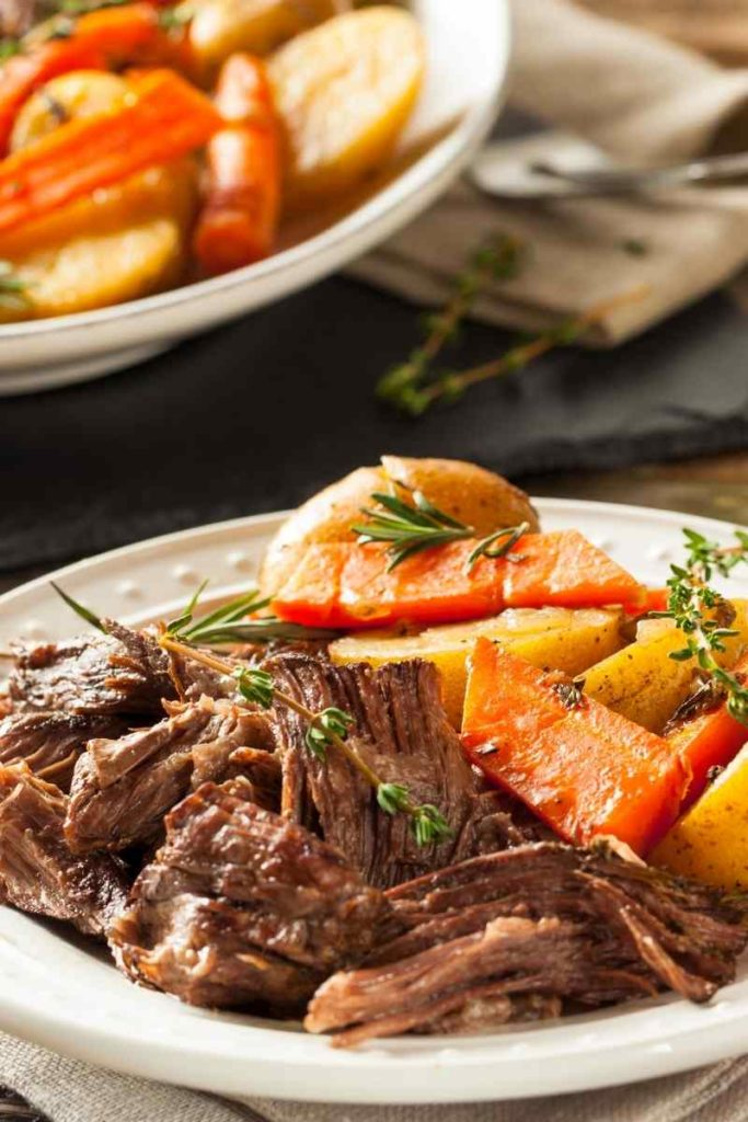 a plate with pot roast and vegetables with a serving platter in the background