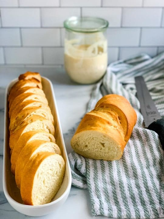 slices of Sourdough French Bread in a white dish with a partially cut loaf on a green and white striped napkin and glass jar of starter in the background