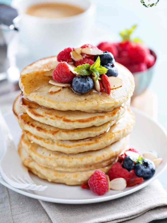 a stack of sourdough pancakes with fresh fruit on top