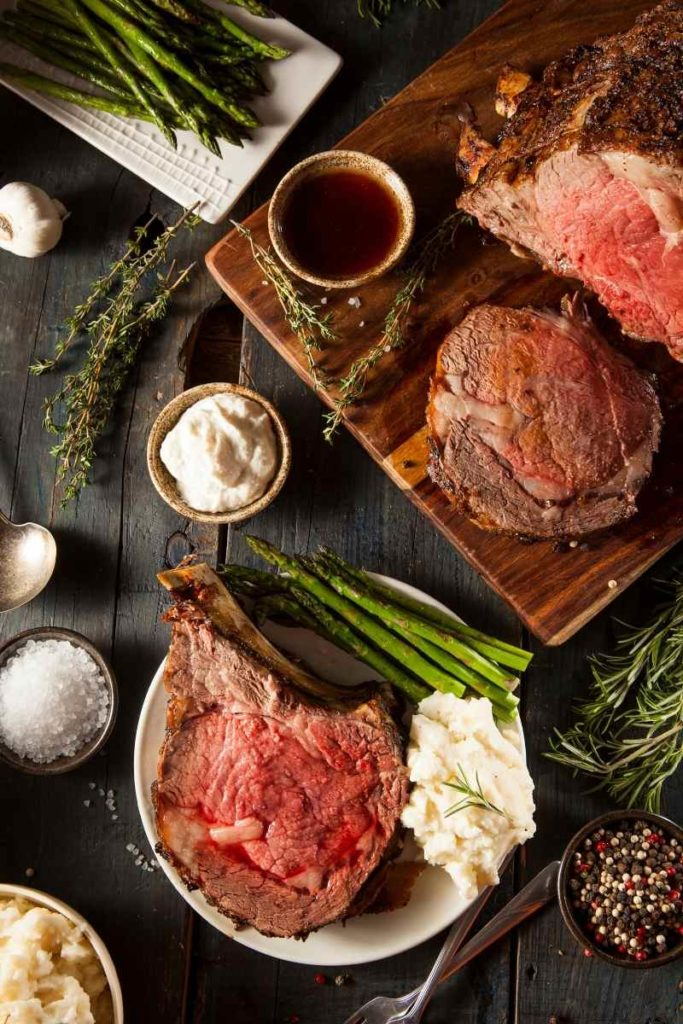 an overlay of a plate of beef rib roast with mashed potatoes and asparagus ready to serve with a cutting board of prime rib sliced
