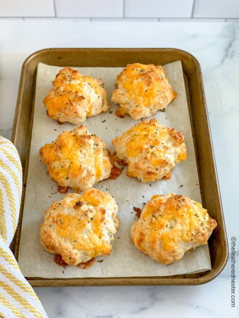 a baking sheet of Bisquick cheddar biscuits with a yellow and white napkin