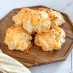 a wooden platter of cheddar bay biscuits
