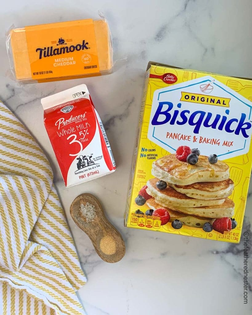 Cheesy biscuit ingredients: a yellow box of Bisquick, a red and white carton of Producers milk,  a block of sharp cheddar cheese, salt, and garlic powder in a wooden tray