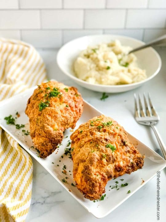 a white platter of Bisquick oven fried chicken breasts and serving bowl of mashed potatoes