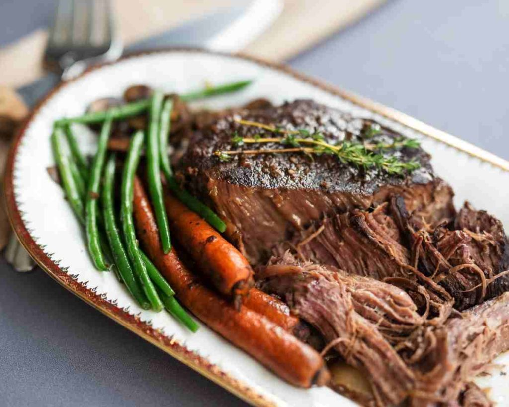 a platter with pot roast and carrots with green beans