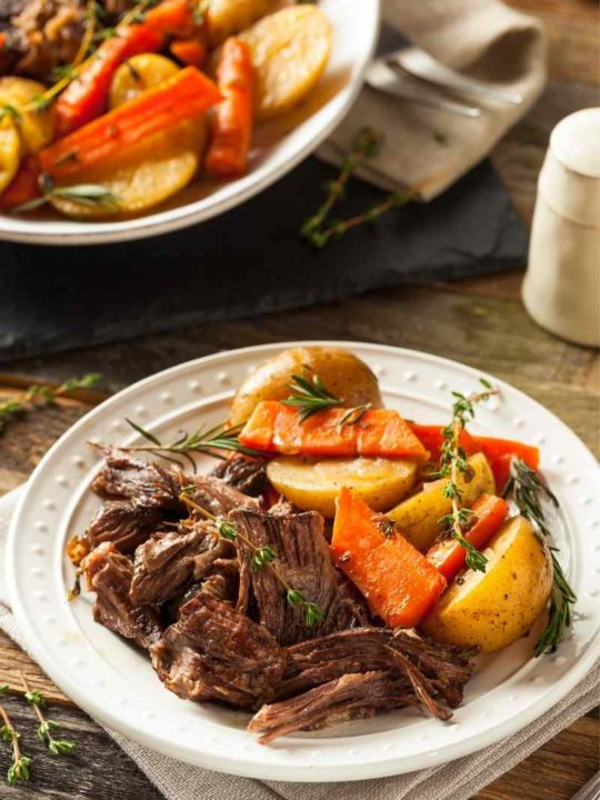 plate of crock-pot pot roast with a serving bowl in the background