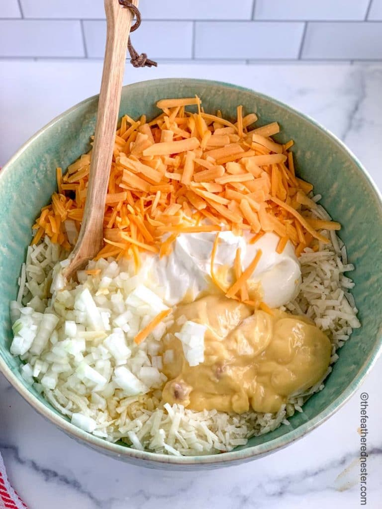 a bowl of hash brown casserole ingredients with shredded potatoes, sour cream, grated cheese, soup, and melted butter