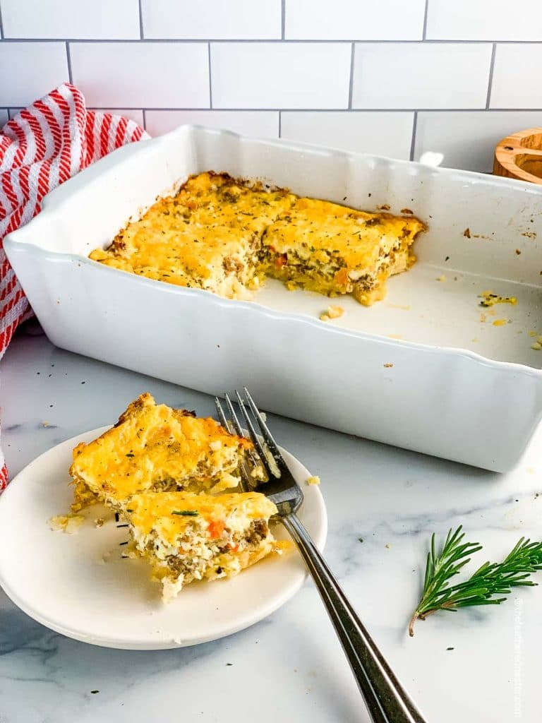 a casserole dish of hash brown casserole with a plate of the egg casserole ready to serve