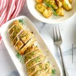 a platter of sliced roasted turkey tenderloin with a bowl of roasted potatoes in the background